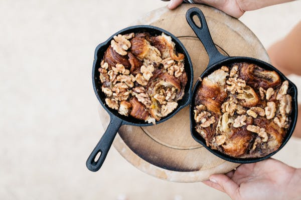 Two mini cast iron skillets on a tray, holding warm caramelized maple walnut croissant pudding.