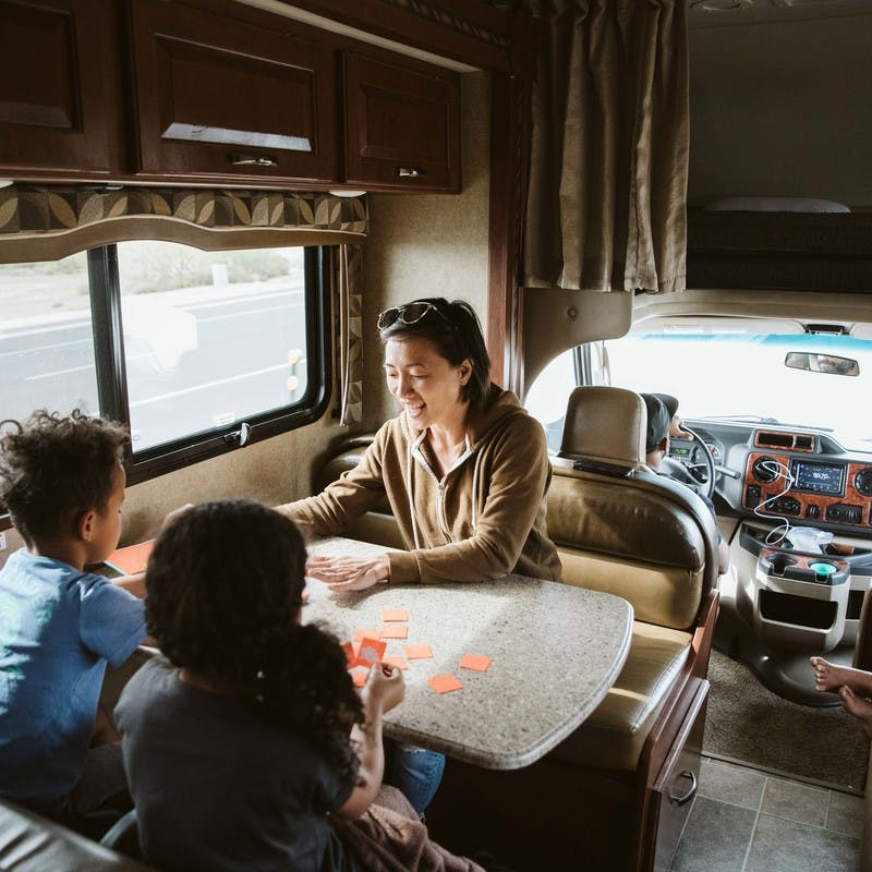 Inside RV, woman in brown jacket sits at table with kids and plays a card game