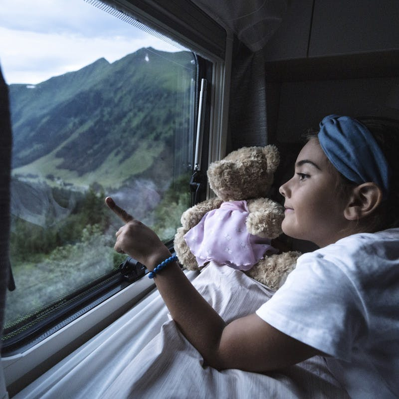 Little girl points out of the window for her family's Class B RV by Hymer.