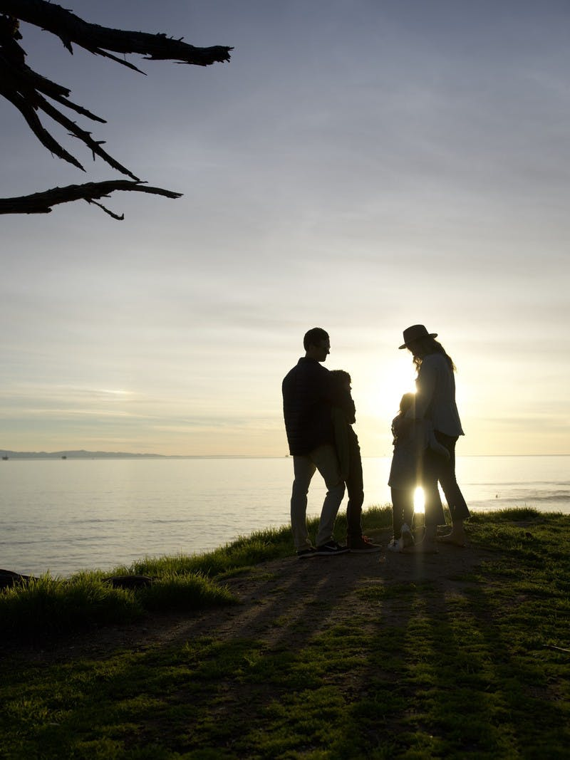 Image of Sarah Schultz and her family overlooking the ocean from a clifftop during a sunset.