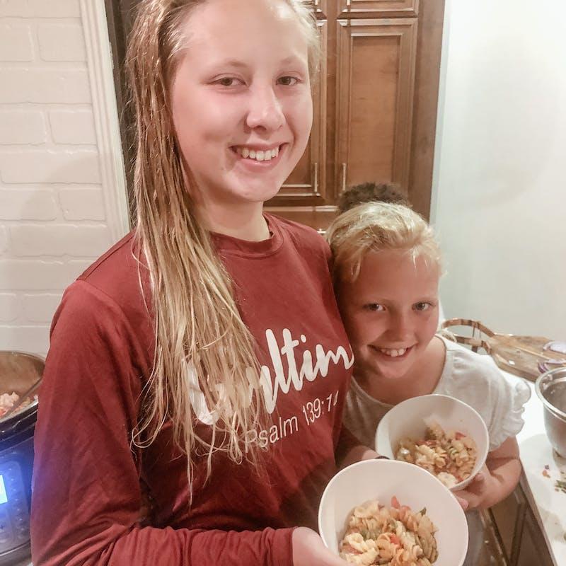Shannon Carew's children hug as they grab some dinner inside their Highland Ridge RV.