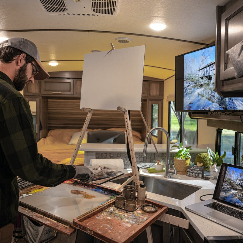 Todd Schabel paints a landscape inside of his RV.