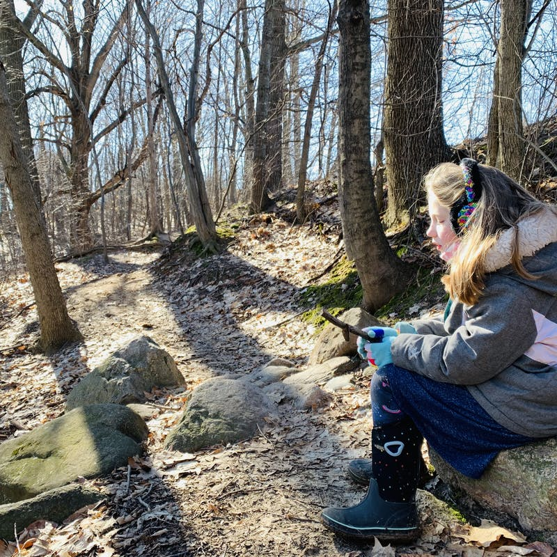 Young girl wearing snow jacket and earmuffs sits on a long and admires a stick