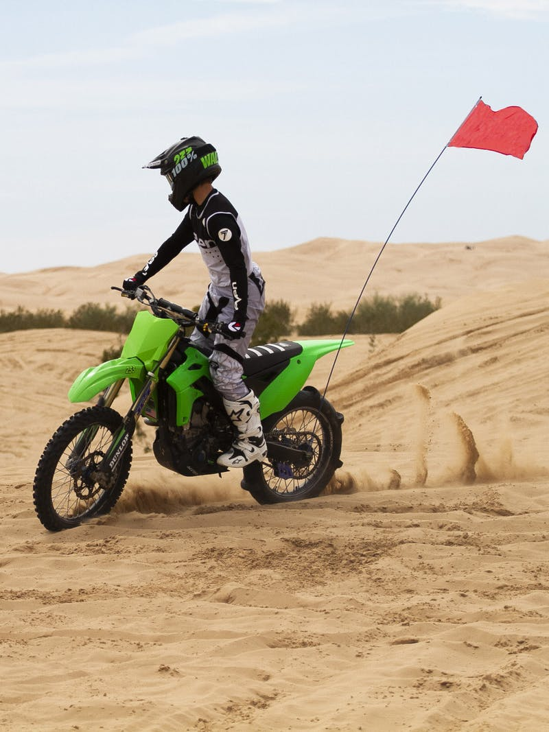 Taylor riding his dirt bike on a sandy dune.