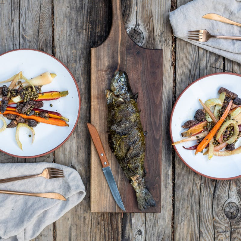 Photo from above of two white plates filled with cooked carrots, morels and fennel, and a full cooked trout wrapped in grape leaves in the middle.