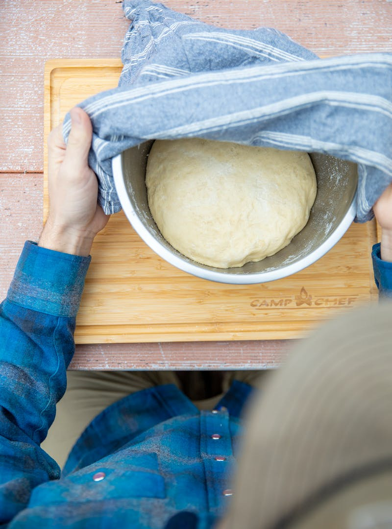 Letting dough rise in a bowl covered with a towel.