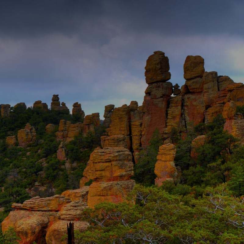 Tall, red Chiricahua mountains stacked on top of each other, surrounded by green trees