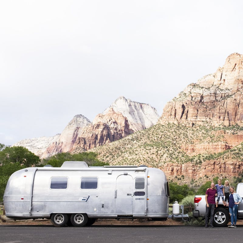 Family standing in front of truck and Airstream travel trailer.  Background includes large rock formations.
