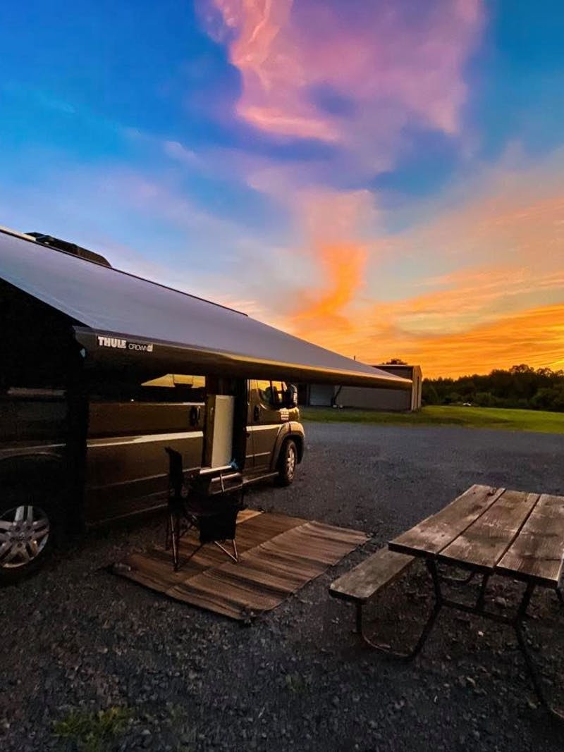 Jess Lawson's Thor Motor Coach Tellaro with the awning out facing a beautiful sunset.