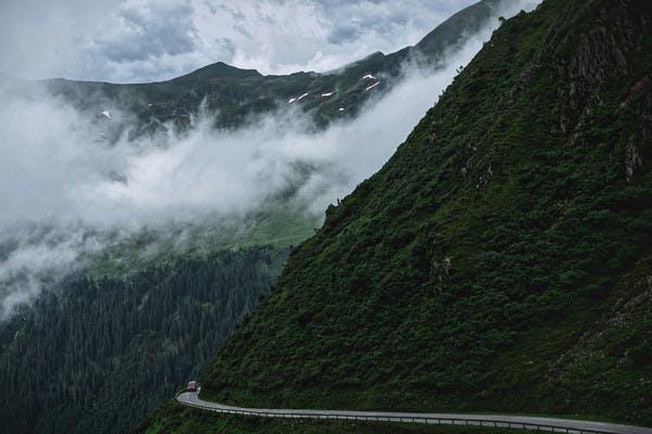 Class B RV drives through through foggy mountain road.