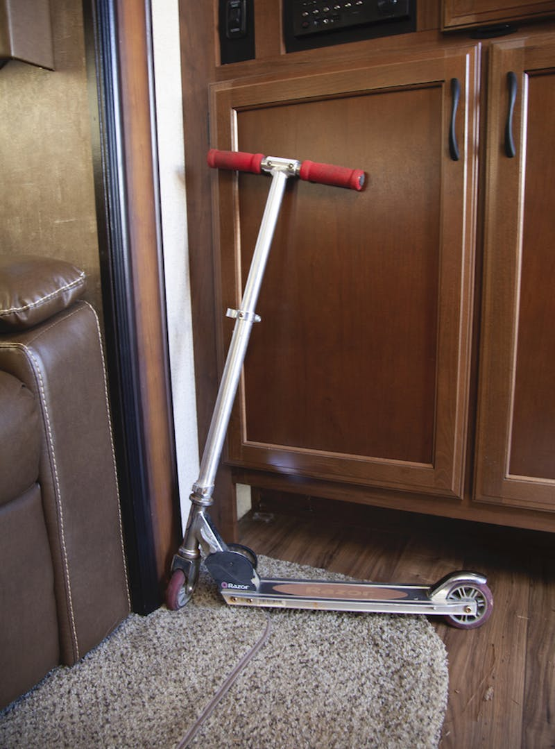 A slim foot-powered scooter leaning against a wall inside an RV.