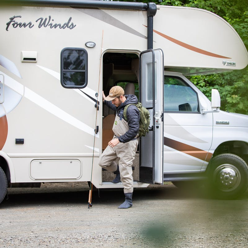 Fisherman with backpack stepping out of Class C motorhome with fishing pole.