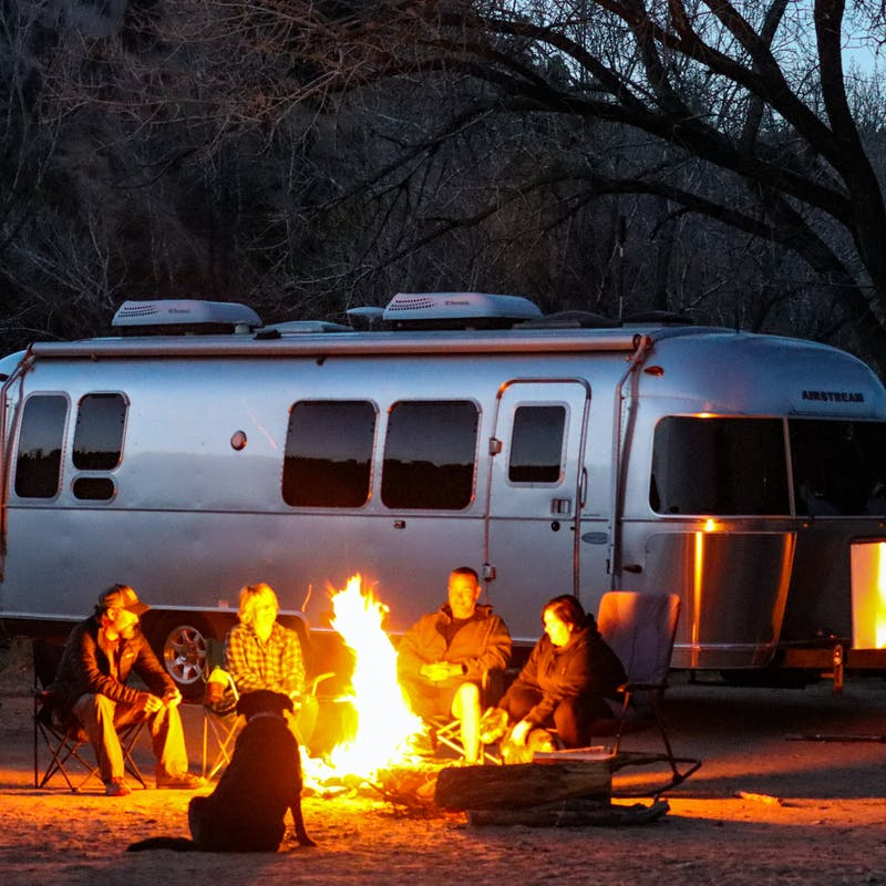 Greg Graham and friends sit at a campfire in front of his Airstream.