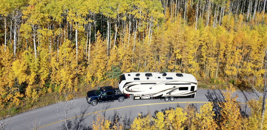 A truck pulling an RV on a tree-lined street.