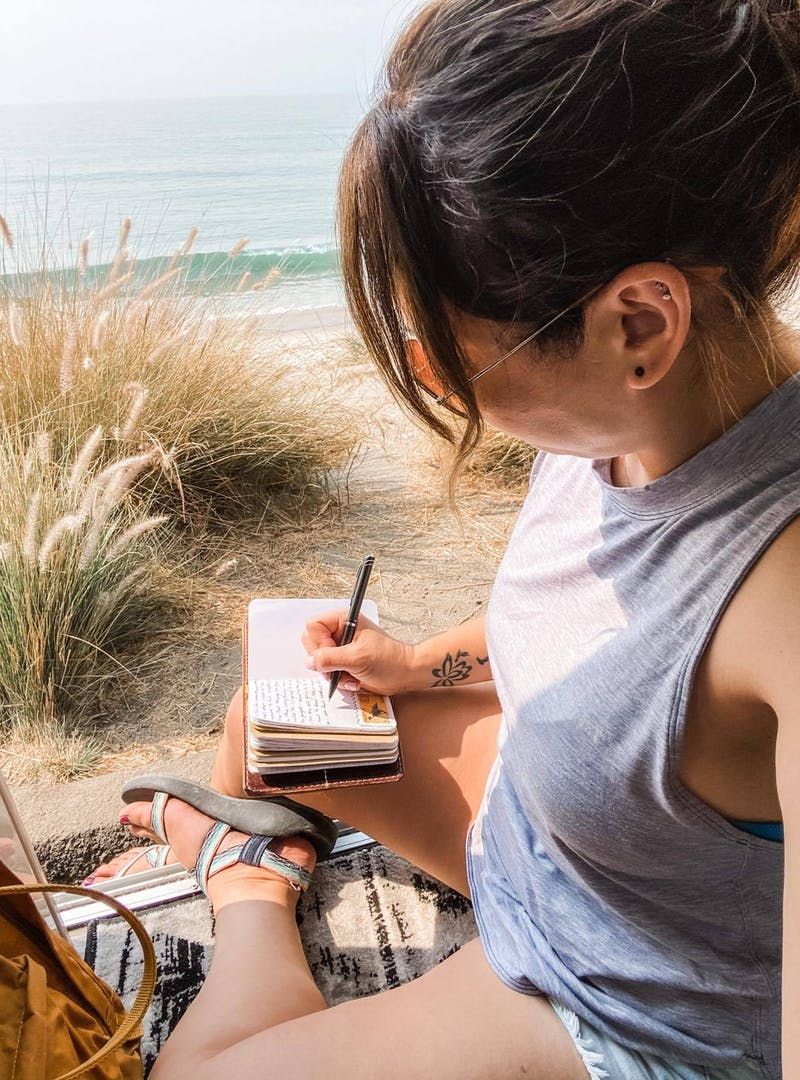 Jess Lawson journaling while sitting in the doorway of her class B RV, a Thor Motor Coach Tellaro.