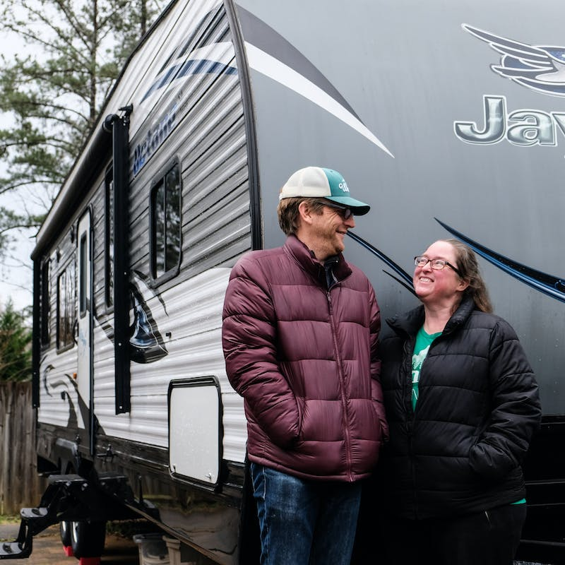 Gretchen Holcomb and her husband smile at each other while they stand in front of their Jayco Octane toy hauler.
