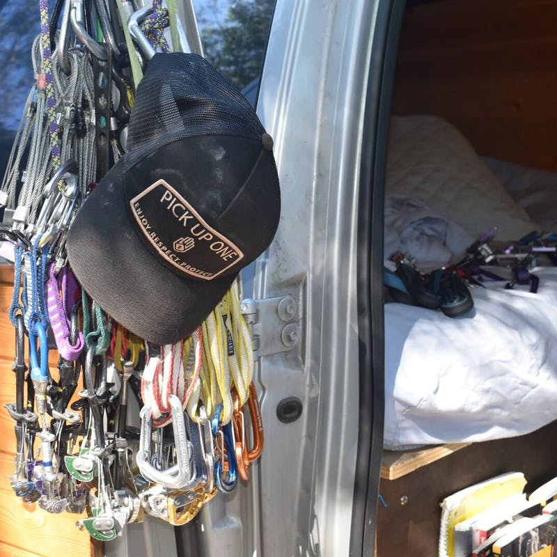 Hat and climbing gear and clips hanging on van
