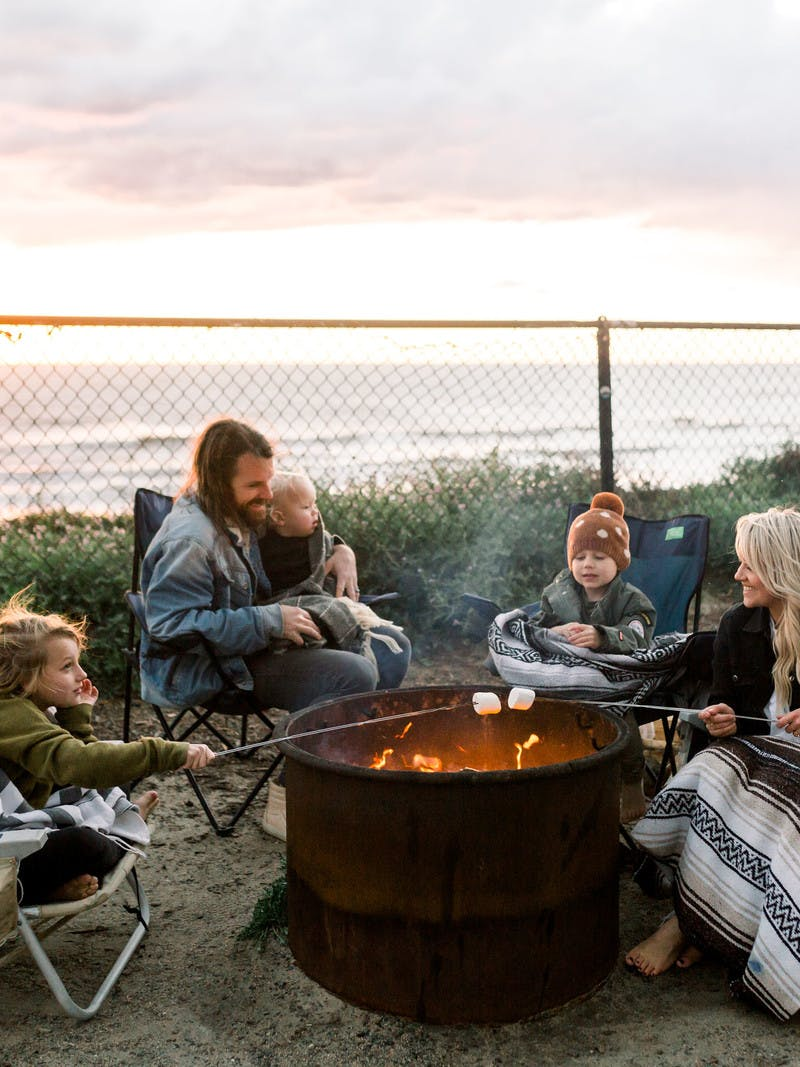 Amber Thrane and her family roasting marshmallows over a fire next to an Airstream Travel Trailer RV, with the ocean in the background.