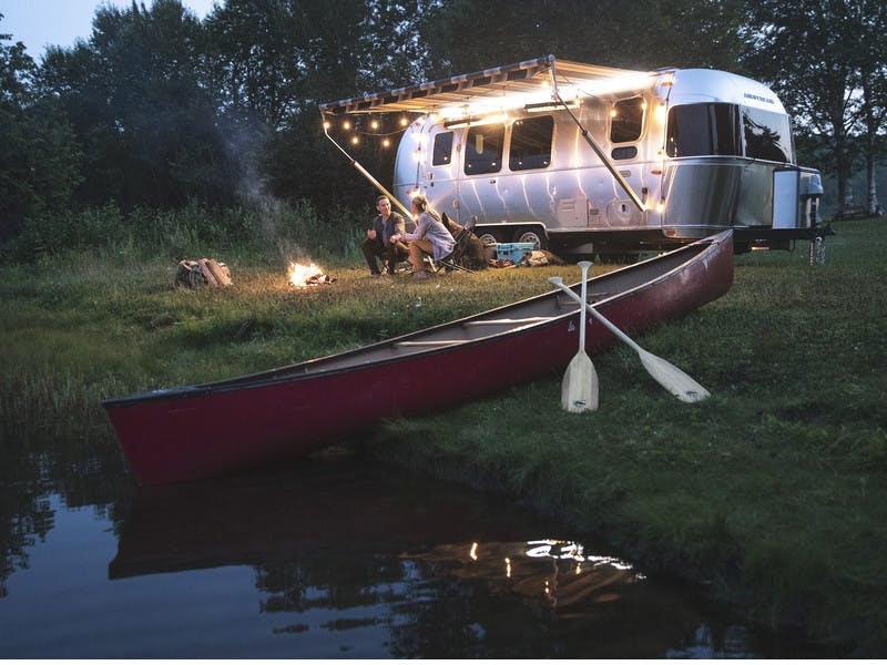 Airstream travel trailer on lake with canoe and couple sitting at a fire with their dog