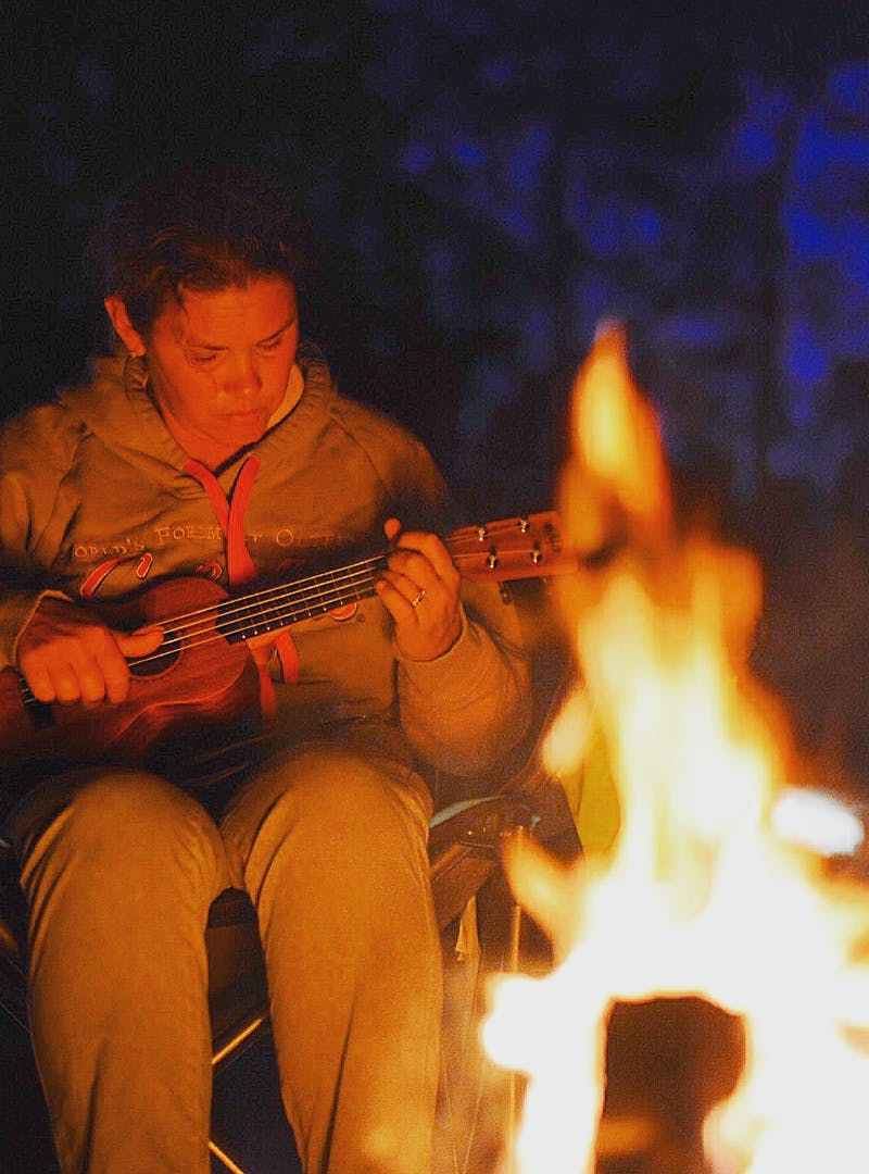A woman playing a ukulele by the fire at night.