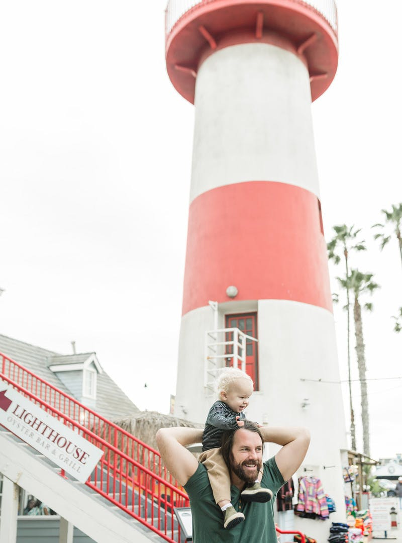 Man holds young child on his shoulders in front of a red and white lighthouse.