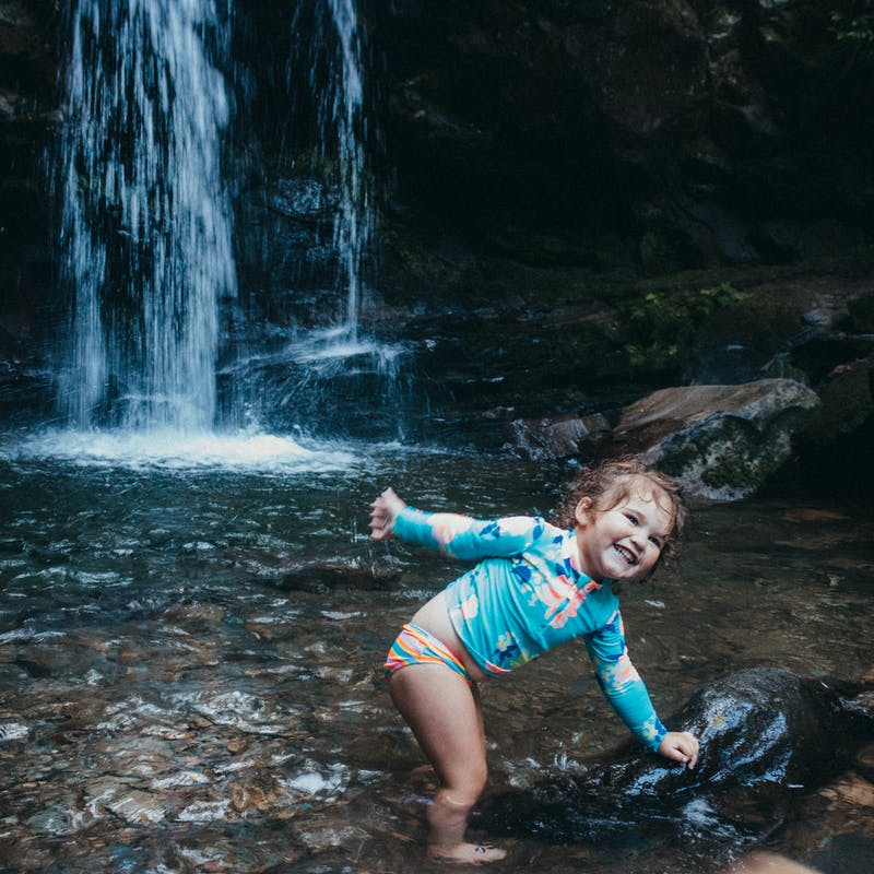 Sammy Seles' young daughter plays in water near a waterfall.