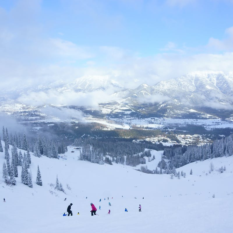 View down a ski lift to snowy slopes with pine trees and cloudy mountains in the background