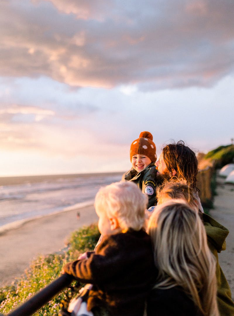 Amber Thrane and her family watching the sun set by a fence, with the beach & ocean in the background.