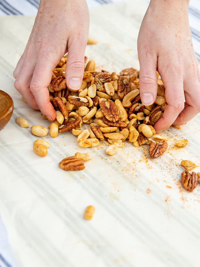 Hands mixing nuts together with cajun spices on parchment paper.