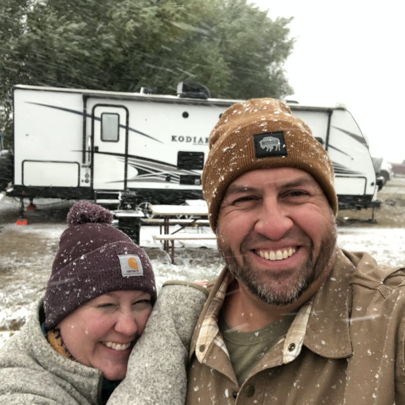 Abby Booth and her husband smile in the snow for a selfie in front of their Dutchmen Kodiak travel trailer.