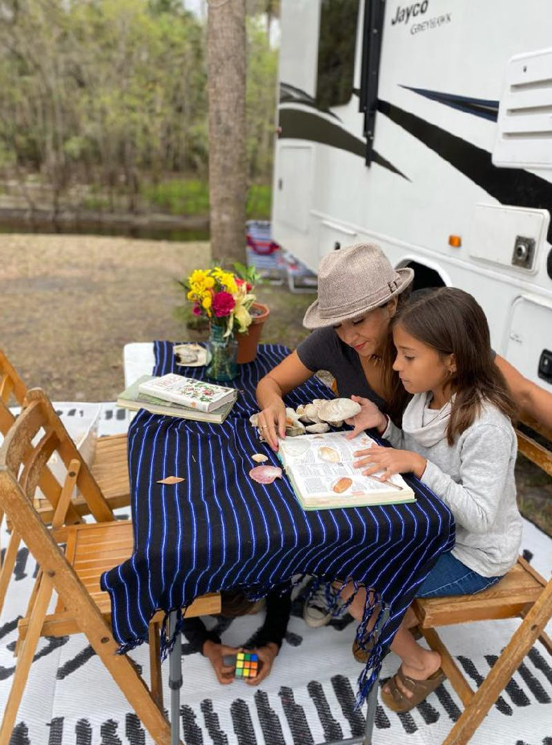Sandra Peña and her daughter sit at a picnic table and identify shells in front of their Jayco Class C RV.