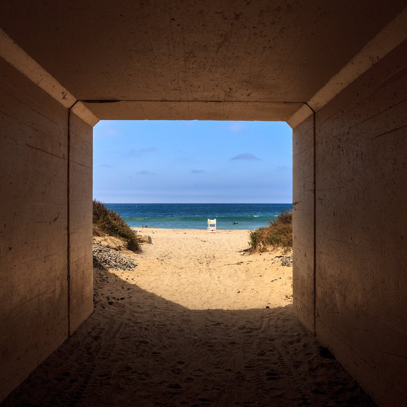 View inside a tunnel looking out at sandy beach, blue ocean and blue sky