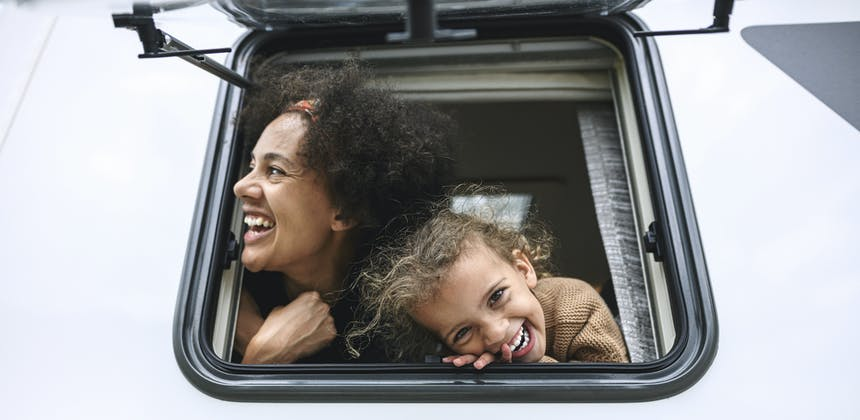 A mother and her daughter stick their head out of a parked RV window while laughing.