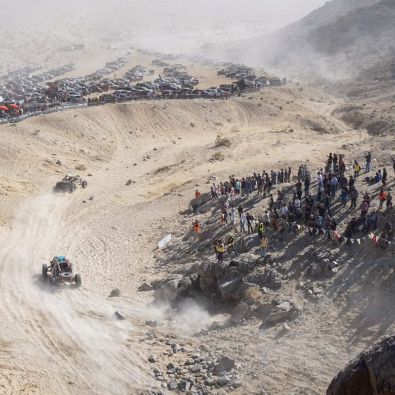 Ultra4 vehicle rounding a section of the path while spectators watch.