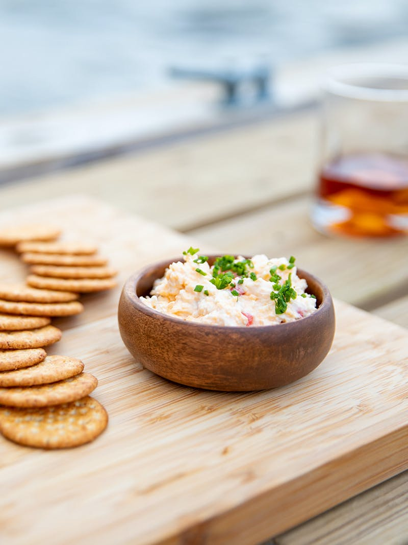 A cheese board with crackers, salami, pickled vegetables and a bowl of pimento cheese spread.