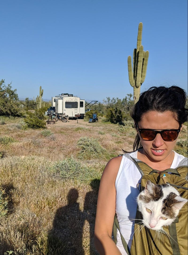 Brittany Ciepluch holding her cat in her backpack while going on a hike near their Keystone Montana fifth wheel.