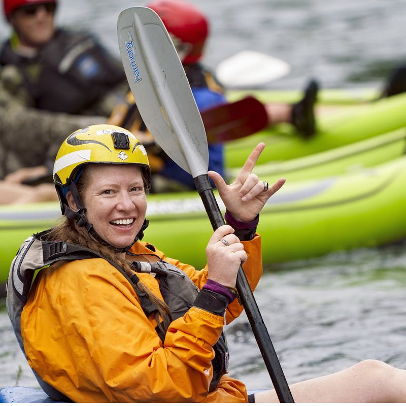"A participant wades in the water in her kayak while throwing up a ""rock and roll"" sign."