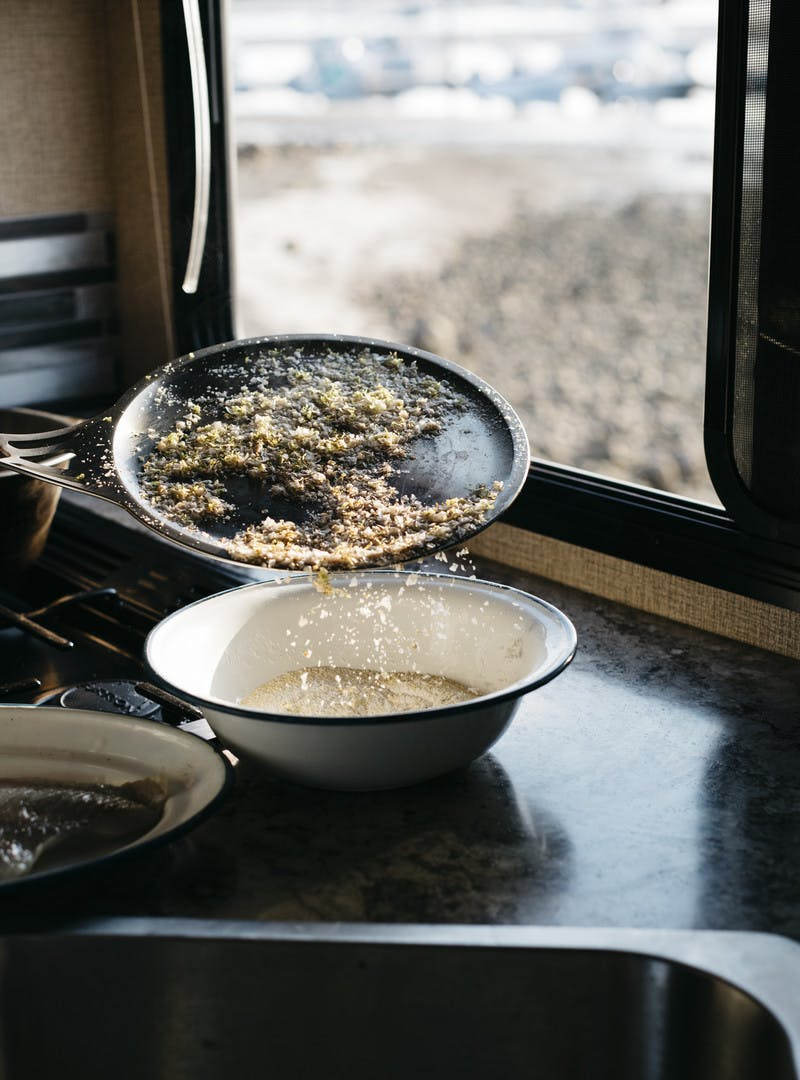 Zest and salt being poured over other seasonings in a bowl inn the RV kitchen.