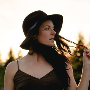 Aubrey Janelle, wearing a black hat and black shirt, holds hair and looks into the distance.