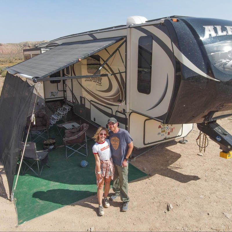 A couple poses in front of their fifth wheel RV