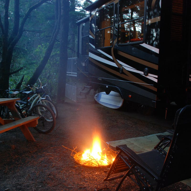 Eric Hannan's RV parked at a campsite next to a fire burning in a pit at night.