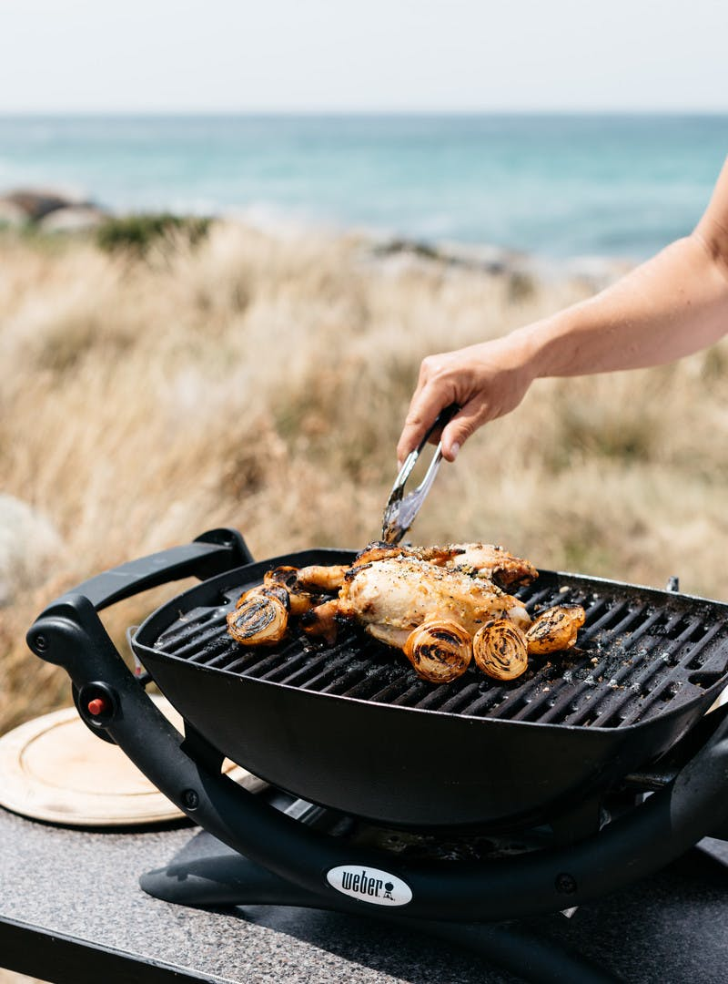 Grilling chicken outside in front of grass and ocean.