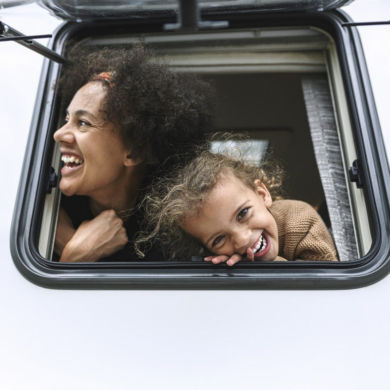 Mother and daughter poke their heads out of the window of their Class B RV by Hymer.