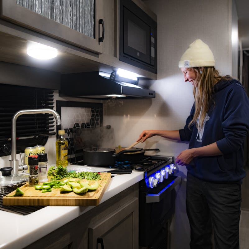 A woman cooks over the stove inside of an RV kitchen.