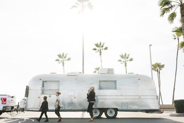 Amber Thrane holding baby, walking in front of Airstream RV, with two kids walking in front and palm trees in the background.