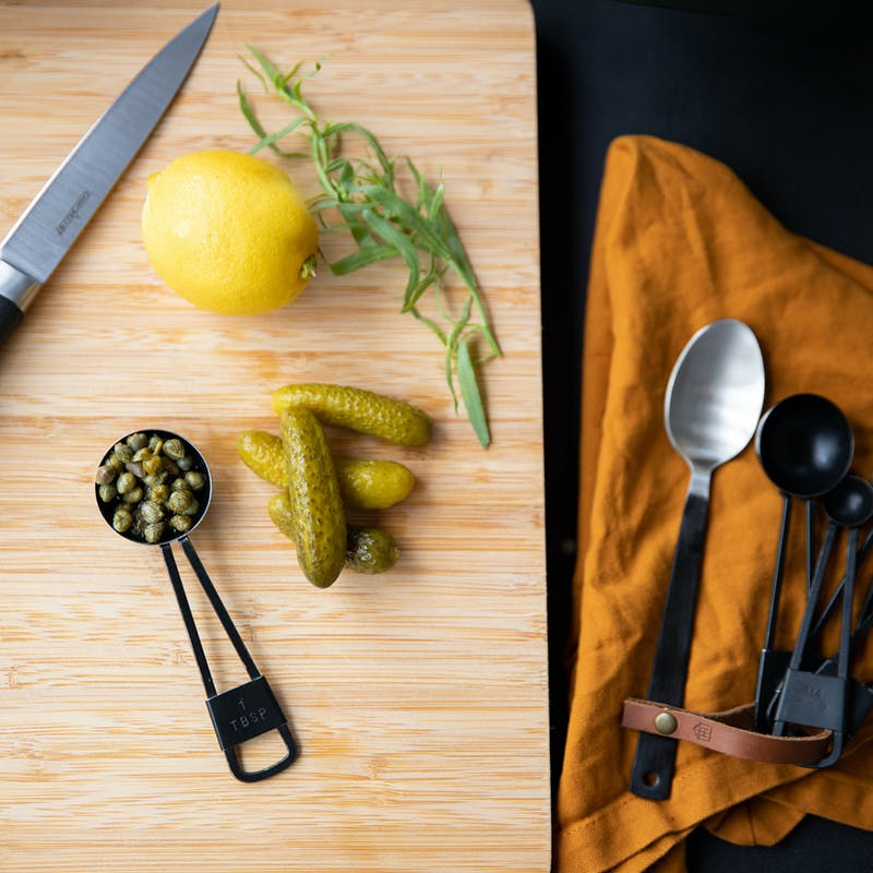 Gherkins, capers, lemon and thyme on a cutting board.