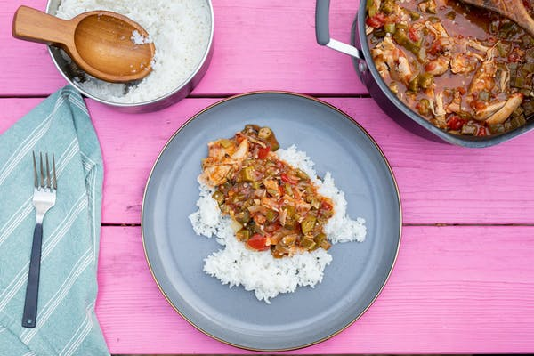 A plate of smothered chicken over rice on a hot pink picnic table.