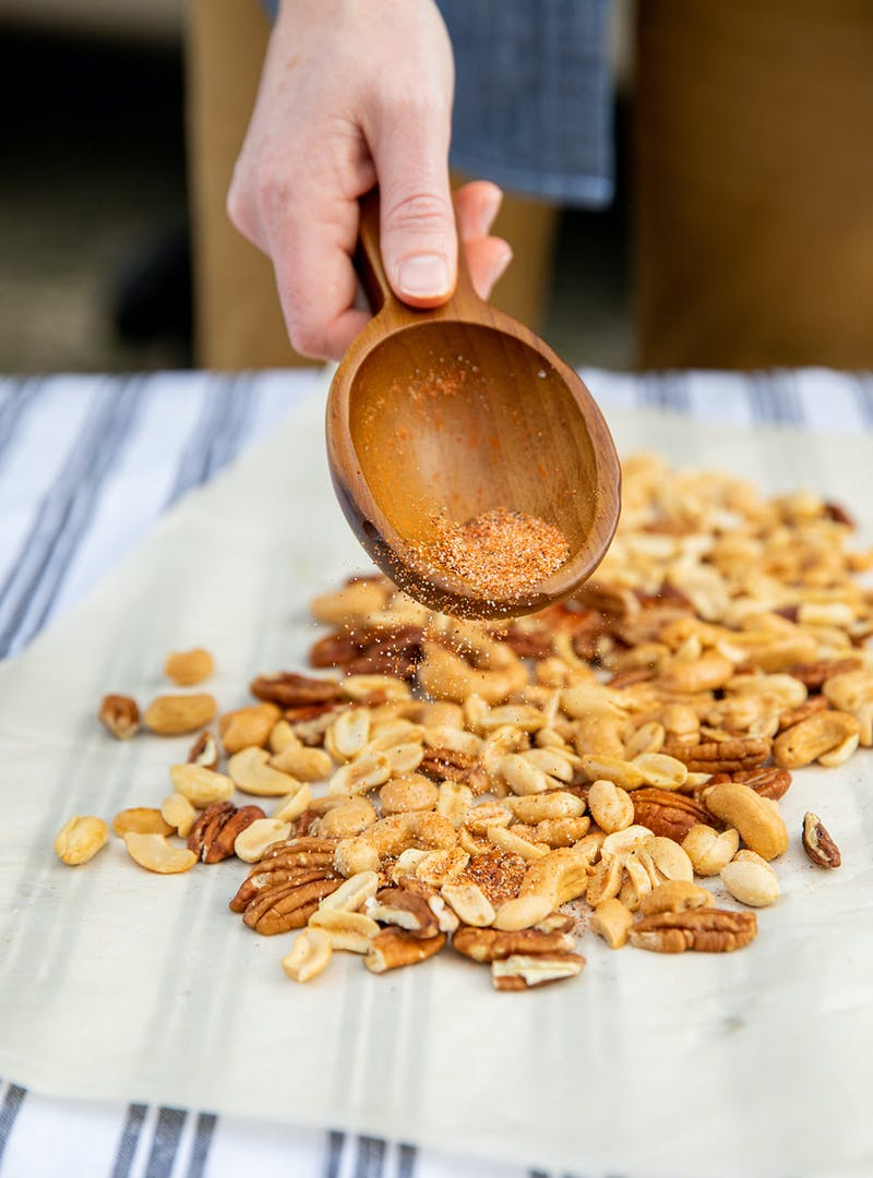 A hand holding a wooden spoon sprinkles spices over mixed nuts.