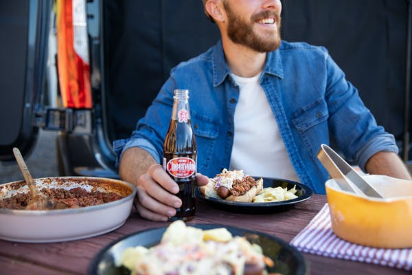 A man smiles holding a soda while sitting at a table and a Carolina Hot Dog plated in front of him.