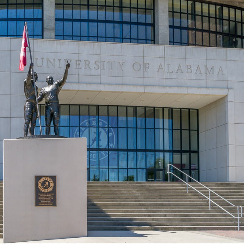 Brick front of Bryant–Denny Stadium at University of Alabama in Tuscaloosa, Alabama, with football player statues and American flag.
